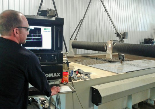 Marcus Henning keeps an eye on this water jet machine as it slices through an aluminum sheet with a 60,000 PSI water stream. It can also cut five-inch steel.
