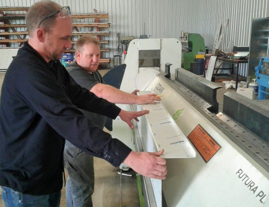 Owner Marcus Henning (left) and his employee Creighton Regenwether operate this computerized folding machine at Architectural Metal Folding in North Liberty. This panel will end up on a new Kansas City building.