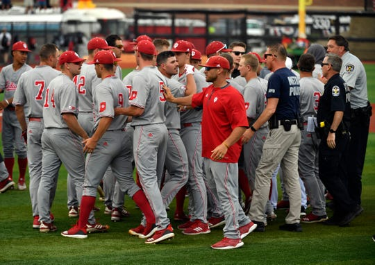 The indiana baseball team is separated from the Louisville team by police following Louisville's 9-7 victory in their NCAA regional game on June 2, 2019.