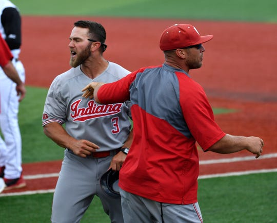 Indiana assistant coach Casey Dykes (3) is led away as he continues to arguea with game officials after a called third strike to end their NCAA regional game against Louisville on June 2, 2019. Louisville won 9-7.