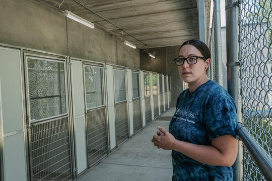 Kate Turner, office manager at the Ingham County Animal Control & Shelter, shows some of the open-air pens and access to the fenced area where dogs and potential adoptive owners can get to know each other Sunday, June 2, 2019.