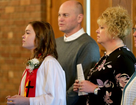 Kat Miller, 14, one of four confirmands, waits to walk into the church with her father, Paul, and mother, Tammy, at Batavia Zion United Methodist Church in Adell on Sunday. She was told by the church not to read what she wrote about her disagreement with the church and its views on homosexuality, so her statement included a disclaimer at the end.
