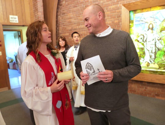 Kat Miller, 14, one of four confirmands, talks to her father, Paul Miller, before her confirmation at Batavia Zion United Methodist Church in Adell on Sunday. Miller stood up to affirm only her non-denominational Christian faith but did not take an oath to become a member of the United Methodist Church in light ofits recent vote to uphold a ban on LGBTQ clergy and marriages.