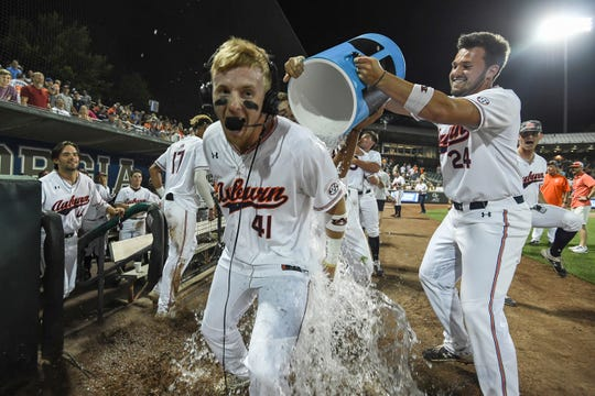 Auburn's Conor Davis (24) dumps a water cooler on Steven Williams (41) after his walk-off home run against Georgia Tech during an NCAA Regional on Saturday, June 1, 2019, in Atlanta, Ga.