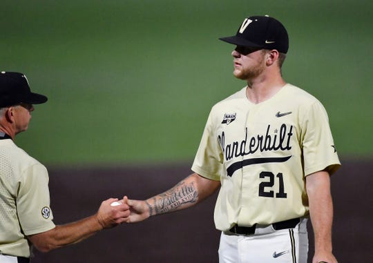 Vanderbilt pitcher Tyler Brown (21) hands the ball to coach Tim Corbin after giving up four runs in the bottom of the ninth inning Saturday.