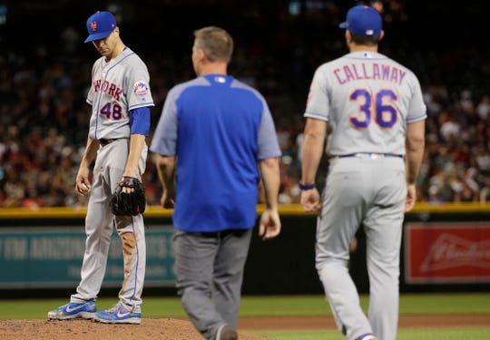 New York Mets manager Mickey Callaway (36) walks to mound with the trainer to check on starting pitcher Jacob deGrom during the seventh inning of the team's game against the Arizona Diamondbacks, Saturday, June 1, 2019, in Phoenix. DeGrom left the game with an injury.