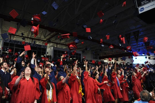 Livonia Franklin graduates toss their hats in the air.