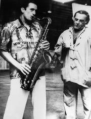 """Jazz saxophonist Georgie Auld, shown instructing Robert DeNiro how to finger a saxophone for his role in the film, """"New York, New York,"""" commissioned Bruce Fessier to ghost-write his autobiography, which never came to fruition."""
