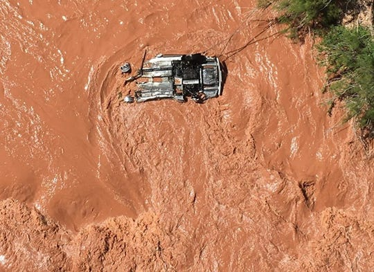 This Friday, May 31, 2019, photo released by the Beaver Dam Littlefield Fire District shows an upside-down vehicle in the Virgin River along Interstate 15 by bridge 7 near Littlefield, Ariz.