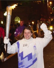 Lyzbeth Glick carries the Olympic torch in honor of her husband Jeremy Glick during the 2002 Salt Lake Olympic Torch Relay Sunday, Dec. 23, 2001, in New York. Jeremy called Lyzbeth from United Airlines flight 93 to tell her that that the plane had been hijacked on Sept. 11. (AP Photo/Suzanne Plunkett)