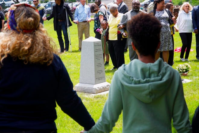 In this Monday, May 27, 2019 photo, a group of people unveil the new headstone for Hark Lay Wales in Cottonwood Heights, Utah.   Wales, a slave who travelled to Utah in the 1800s to settle the territory on behalf of the Mississippi couple who owned him was honored during the ceremony that unveiled a headstone at his burial site that was an unmarked grave for 130 years.(Sam Penrod/KSL TV via AP)