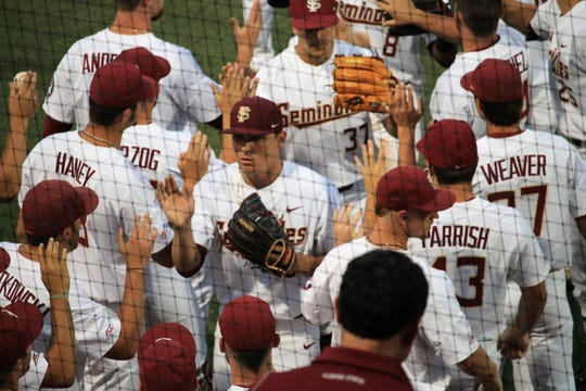 FSU players congratulate C.J. Van Eyk after an inning during FSU baseball's game against Georgia in the Athens Regional.