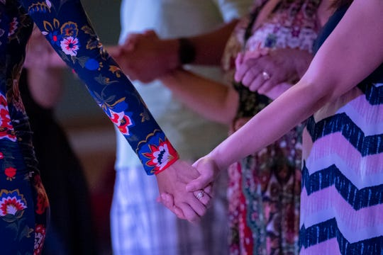 Congregants hold hands in prayer during a service at Lifehouse Virginia Beach Church on June 2, 2019.
