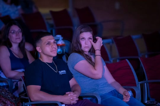 Samantha Estrada wipes a tear from her eye while watching Pastor Brandon Shank deliver a sermon for Lifehouse Virginia Beach Church with her husband, Rudy.
