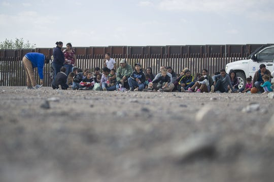 Migrants wait to be processed and loaded onto a bus by border patrol agents after being detained when they crossed illegally into the U.S. from Mexico in Sunland Park, N.M.