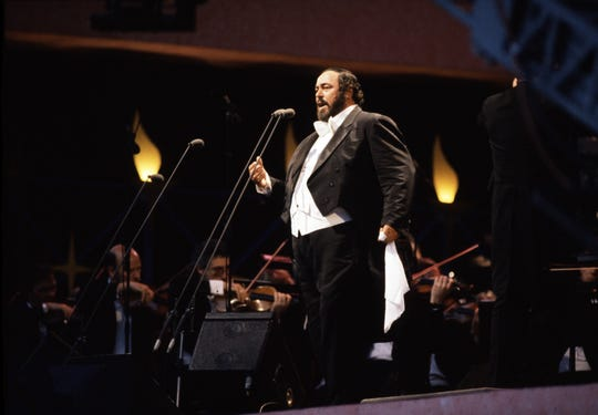 Pavarotti performs for tens of thousands of fans, and Princess Diana, at 1991's rain-soaked Hyde Park concert in London.