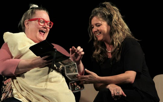 """Nadine (Jen Burns, left) shows photos of her kids named for famous people to Lucille (Tracy Brown) in this rehearsal scene from Abilene Community Theatre's """"Dearly Departed."""""""