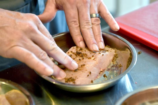 Gavin Baker puts a rub of spices on a sturgeon filet in his apartment home test kitchen on April 18, 2019.