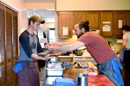 Travis Schultz holds a tray for Gavin Baker to lay out cuts of fish as he butchers a sturgeon in his apartment home test kitchen on April 18, 2019.