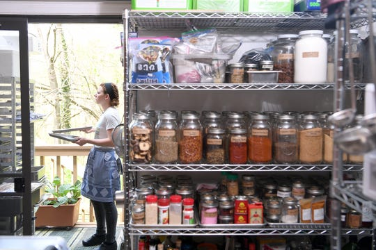 Shannon McKinney looks for a place to store a tray on the porch of Gavin Baker's apartment home test kitchen as she prepares dessert recipes for Noble Cider's The Greenhouse menu on April 18, 2019. The jars of spices in the test kitchen are now a part of the downtown restaurant kitchen.