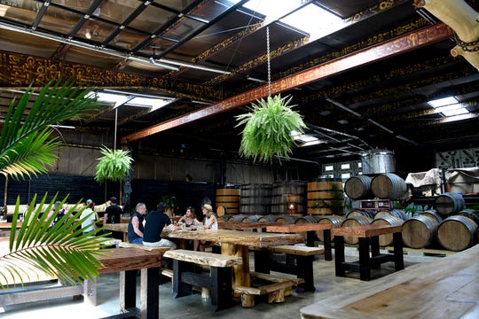 The interior of at Brouwerij Cursus Keme features large wooden tables and natural decor.