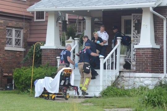 A woman injured in a Monday morning shooting is taken from a home on Lathrop Avenue to a waiting ambulance.
