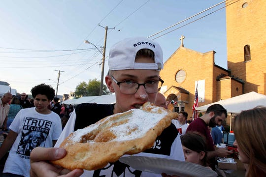 An attendee of St. Anthony of Padua's Italian Feast Days eats pizza fritte on June 10, 2017.