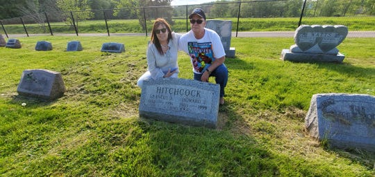 Siblings Elaine Petitclerc and Tim Greenwalt visit the grave of their parents, Howard and Frances Hitchcock.