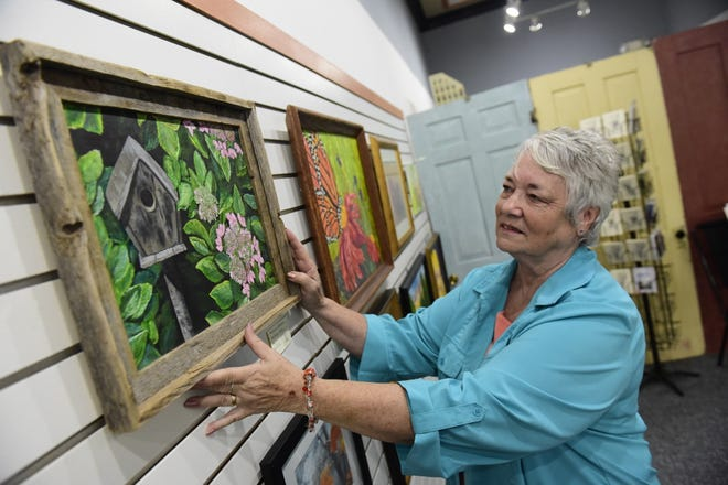 Carolyn Kelley, of Bucyrus, hangs her painting, Cabin at Lakeside, inside the new location of the Brush and Palette art gallery in Galion.