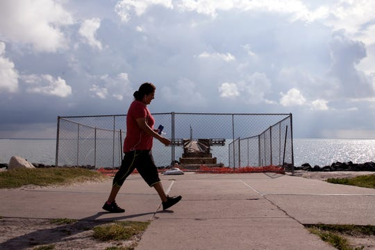A woman walks past the Cole Park Pier on Monday, June 3, 2019, the pier has been closed since 2018. Residents approved a bond to make improvements to the pier and the Corpus Christi Parks & Recreation department is conducting an online survey seeking community feedback to design the pier and determine what improvements will best serve the community.