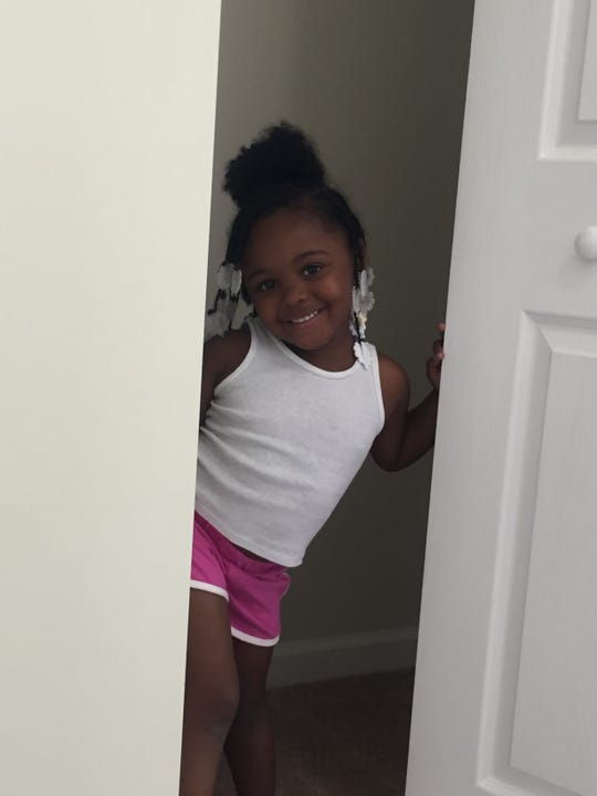 Dennyleona Perry, age 3, smiles as she hides in a closet in her family's new house in Whitman Park.