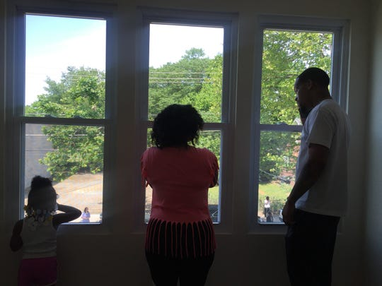 The Perry Family - daughter Dennyleona, mother Janisa and father Dennis - look out a bedroom window at their new house in Camden's Whitman Park neighborhood.