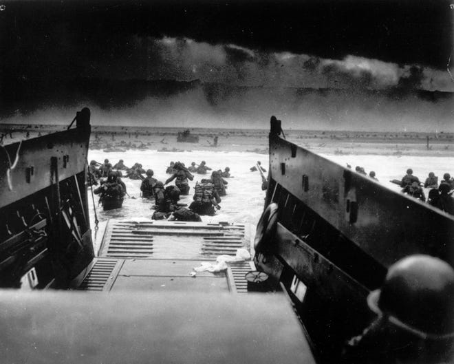Under heavy machine gun fire, American soldiers wade ashore to the beaches of Normandy, France June 6, 1944, during the Allied invasion of Normandy.