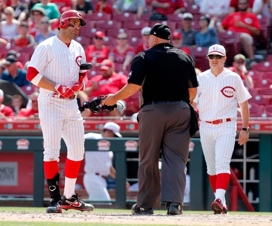 Jun 2, 2019; Cincinnati, OH, USA; Cincinnati Reds first baseman Joey Votto (19) looks at home plate umpire Eric Cooper (middle) after a call during the eighth inning against the Washington Nationals at Great American Ball Park. Mandatory Credit: David Kohl-USA TODAY Sports
