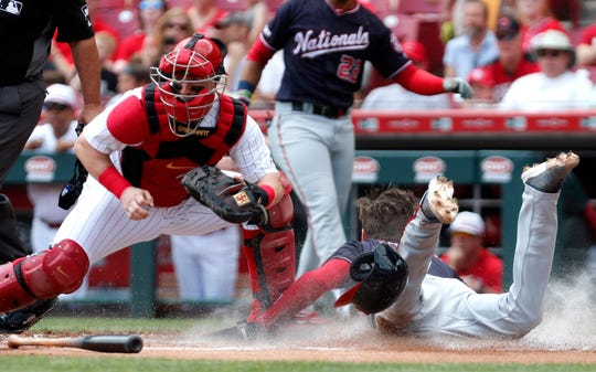 Jun 2, 2019; Cincinnati, OH, USA; Washington Nationals shortstop Trea Turner (7) scores a run past Cincinnati Reds catcher Tucker Barnhart (16) during the first inning at Great American Ball Park. Mandatory Credit: David Kohl-USA TODAY Sports