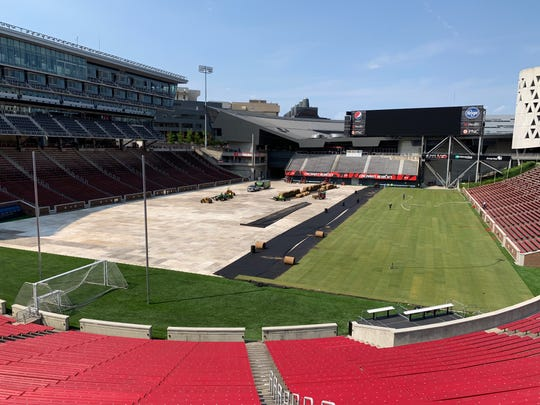 Contractors install a temporary grass surface at the University of Cincinnati's Nippert Stadium Monday, June 3 in preparation for a U.S. men's national team match against Venezuela.