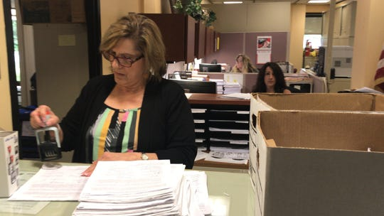 Edison Township Clerk Cheryl Russomanno stamps 4,958 petitions signed by registered township voters. The petition demands an ordinance or referendum to retain township control of the sewer systems in opposition to a proposed $851-million 40-year deal with Suez North American.