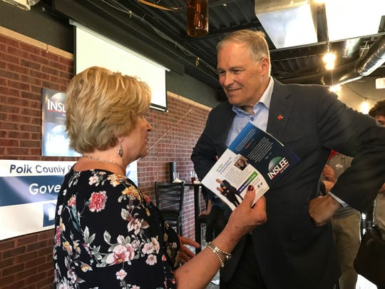 Washington Governor Jay Inslee speaks with Linda Smith, a member of the Urbandale Area Democrats, during a campaign stop at Beerhouse in Urbandale.