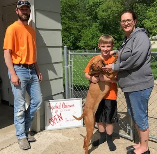 Hooked Up Outdoors bait and tackle shop in Norwalk owners and operators Nate Gute, (L), Michele Kane (R) with son Dayce and pup Georgia.