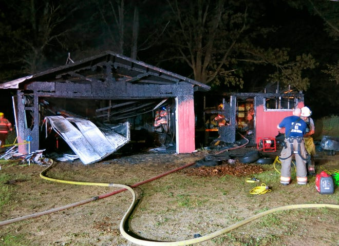 In this Sunday, June 2, 2019, photo, firefighters work at the scene of a fire on Black Highway in the Lenawee County community of Raisin Township, Mich. Authorities say two boys died following the fire at the cabin. The cause of the fire is under investigation.