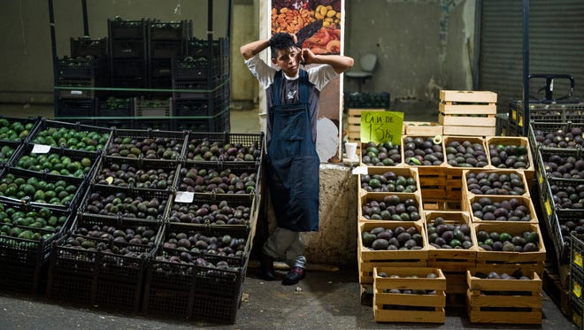 In this Aug. 9, 2016 file photo, an avocado vendor talks on his cellphone at a market in Mexico City.