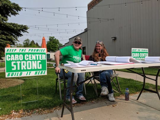 Katie Ozorowicz, 28, and Reamy Berlin, 41, collect signatures for a Caro Center petition on May 31, 2019.