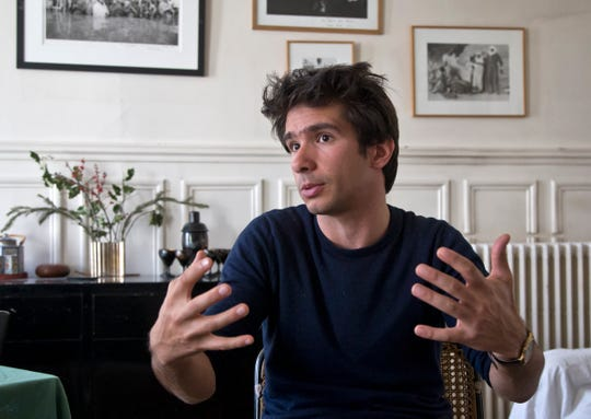 In this April 11 2019 file photo, Lawyer Juan Branco who co-authored a legal document alleging crimes against humanity by the European Union as he speaks during an interview with The Associated Press in Paris, France.