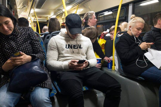 In this photo taken on Thursday, May 16, 2019, passengers look at their smartphones as they ride a bus in Moscow. Russia's communications regulator says that Tinder is now required to provide user data to Russian intelligence agencies.