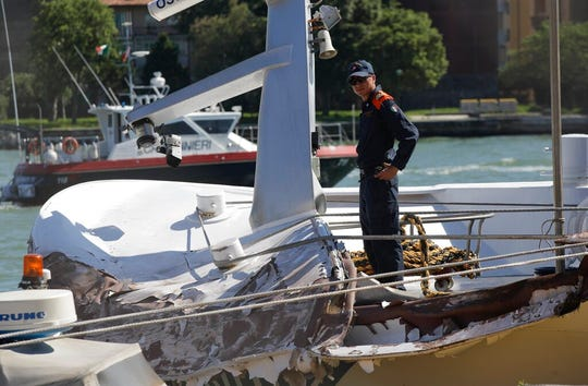 An Italian Coast Guard officer stands on the tourist boat that was struck by a cruise line ship in Venice, Italy, Sunday, June 2, 2019.