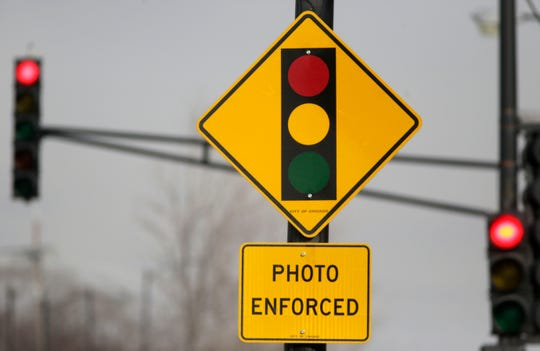 In this Tuesday, Feb. 10, 2015 file photo, a sign warns motorists of the presence of a red light camera in Chicago.