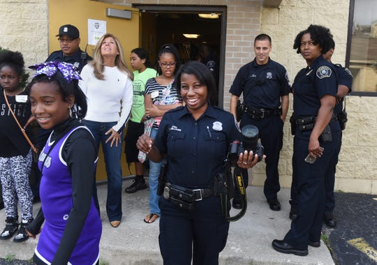 Detroit police officer Elaine Williams, center, prepares to photograph Shaday Jenkins during the Pictures of Hope program by photojournalist Linda Solomon on Sept. 26, 2015.