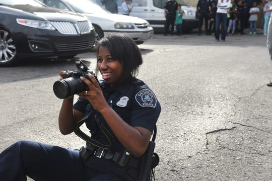 Detroit police officer Elaine Williams gets on ground level as she photographs teammate Shaday Jenkins during the Pictures of Hope program by photojournalist Linda Solomon on Sept. 26, 2015.
