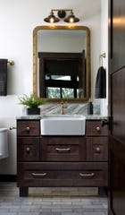 AT HOME for release MAY 2019 HOME TOUCH Caption 04: First-place winner of the 2019 National Kitchen and Bath Association's Design Competition in the Small Bath category, this vanity area features a small farmhouse sink in a freestanding dresser. Designed by Lora Weaver of Inexteriors Design in Seattle, the vanity's lighting, plumbing, mirror and cabinetry fixtures have been selected to emulate warm metal tones.