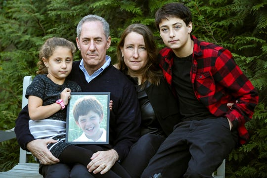 "Nancy Goodman and Mike Froman, and their children, Sarah, Ben, with a photo of Jacob in Washington. Goodman begged eight companies to let her young son try experimental medicines for a brain tumor that ultimately killed him, and ""only three of the companies even gave me a reason why they declined,"" she said."